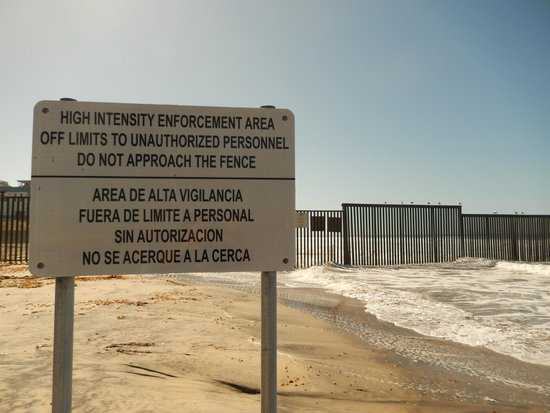 Photo of a signpost threatening violence outside the gated border.